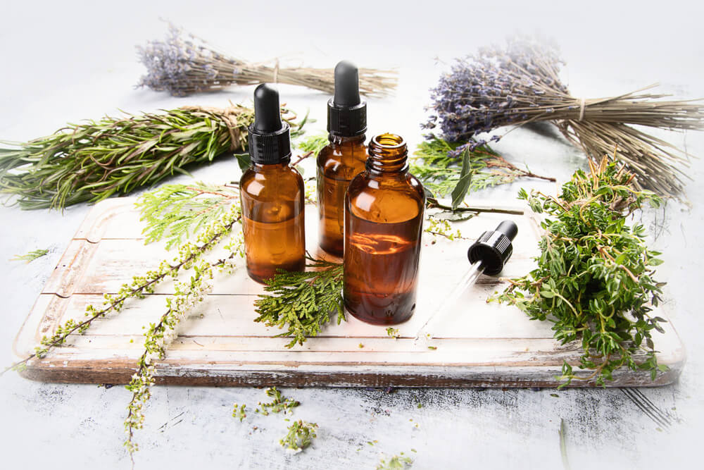 Essential oils in small bottles, surrounded by loose lavender
