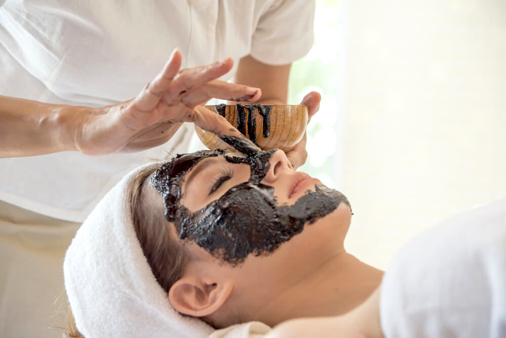 Woman enjoying charcoal facial mask in spa