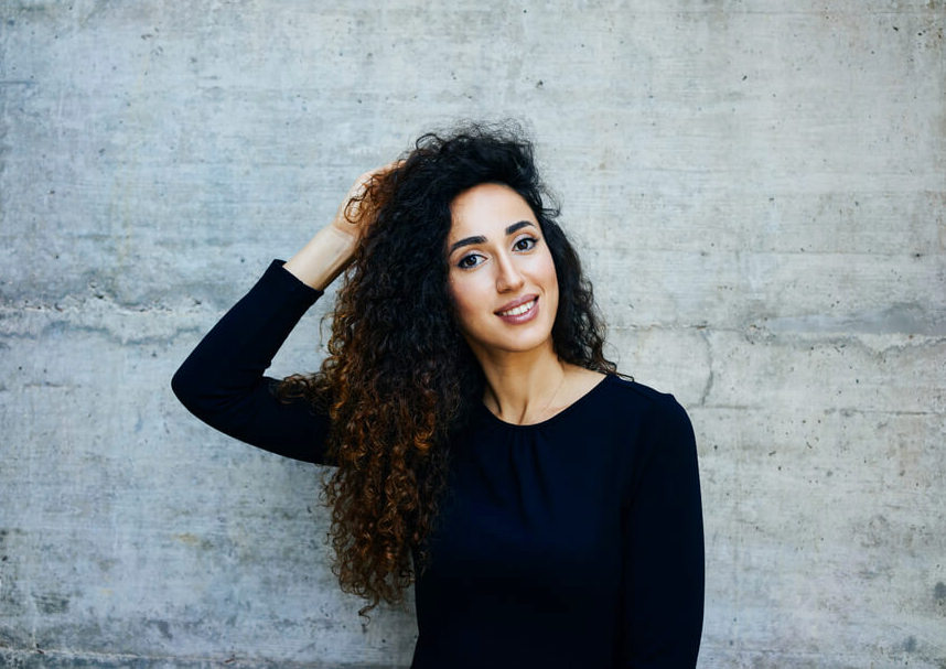 Young woman smiling and touching her curly long hair