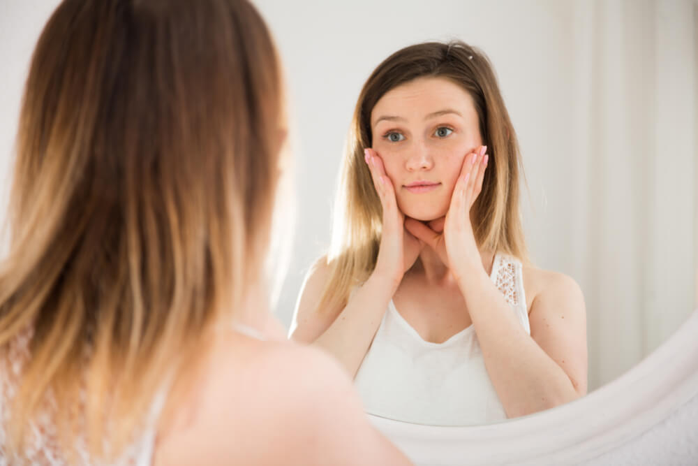 Young woman touching face in front of mirror