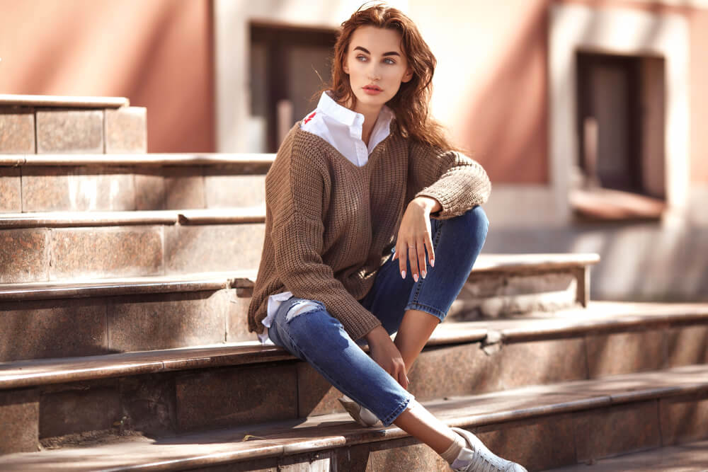 Fashionable woman sitting on outdoor steps