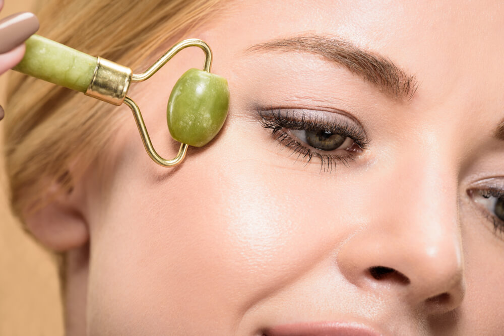 Massaging eye area with jade roller