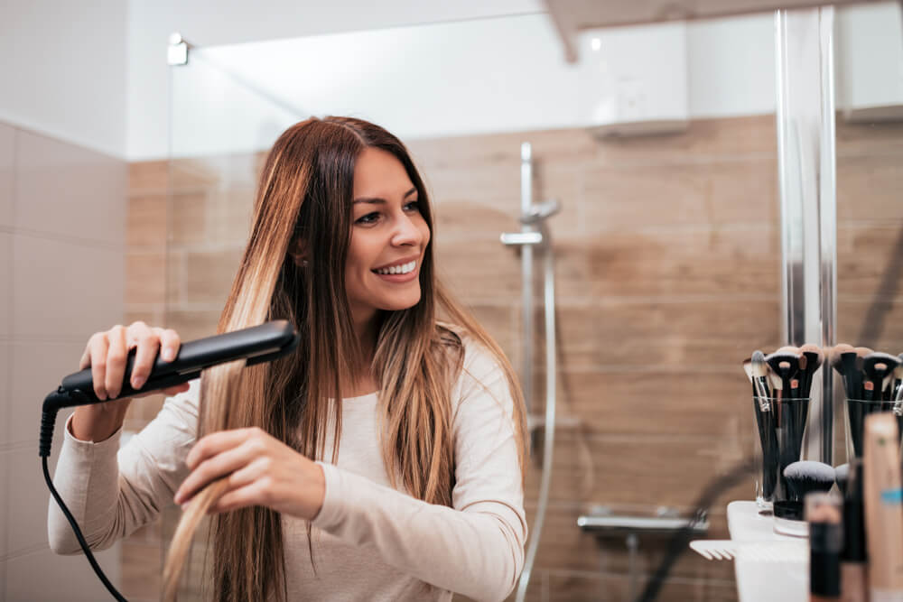 Smiling woman using hair straightener in the bathroom