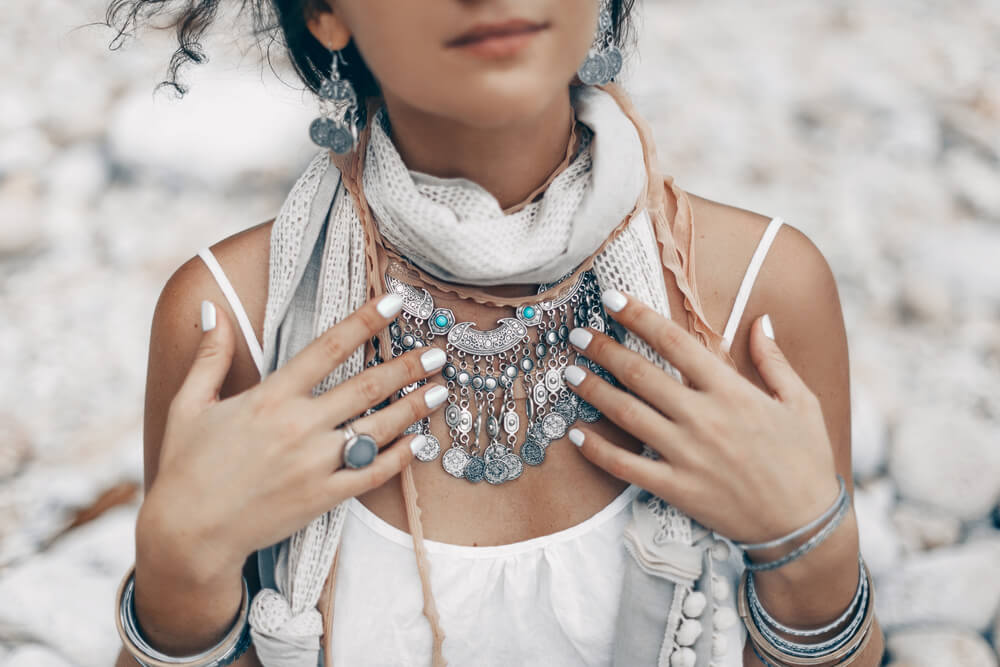 Unknown bohemian woman touching her necklaces