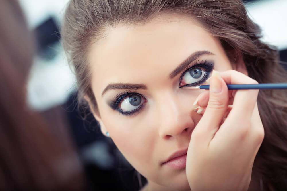 Woman applying black eyeliner to lower waterline