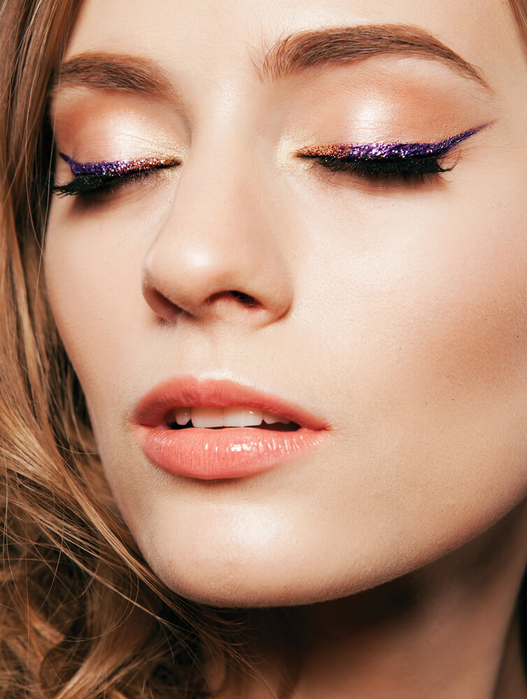 Woman with purple glitter eyeliner and beige eyeshadow