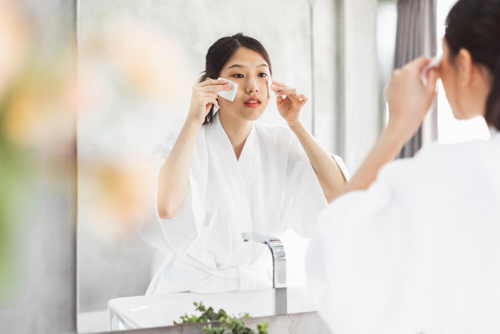 Woman applying skincare with cotton pads