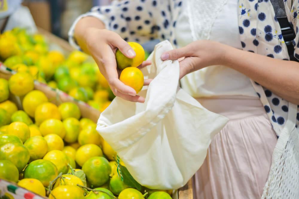 Woman putting fruit into reusable produce bag