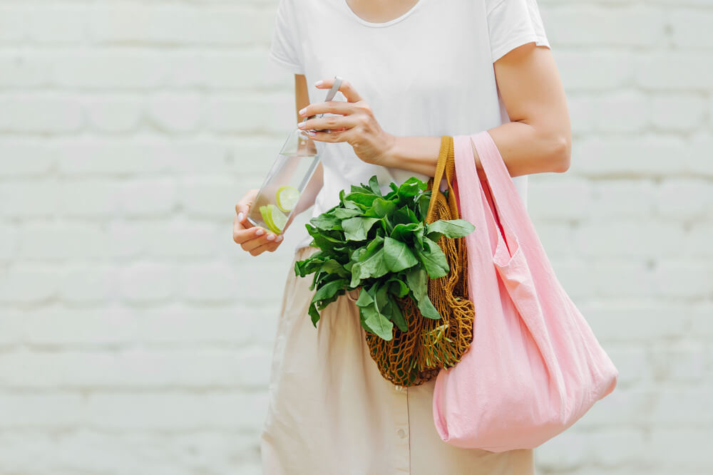 Woman holding reusable bags with groceries
