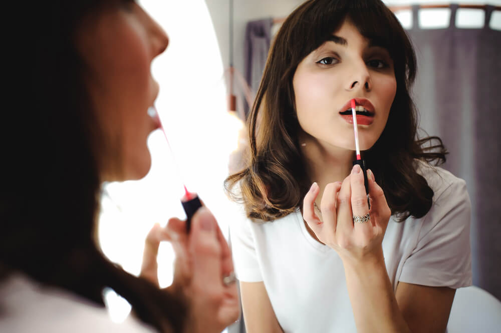 Woman applying lipstick in front of mirror