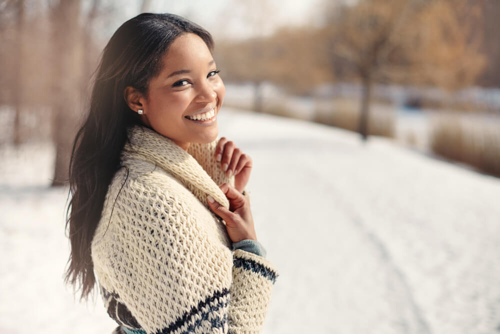 Woman smiling wearing sweater in winter