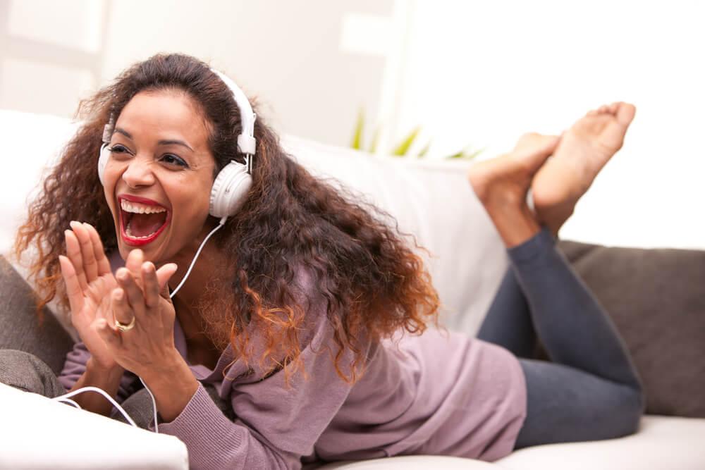 Woman lying on sofa with headphones on looking happy