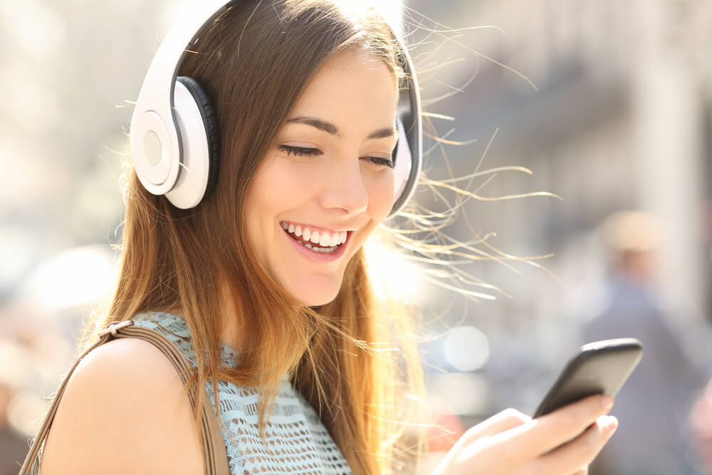 Woman looking at phone with headphones on and smiling