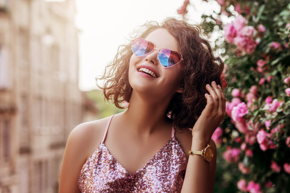 Woman laughing with heart-shaped sunglasses and sequin top