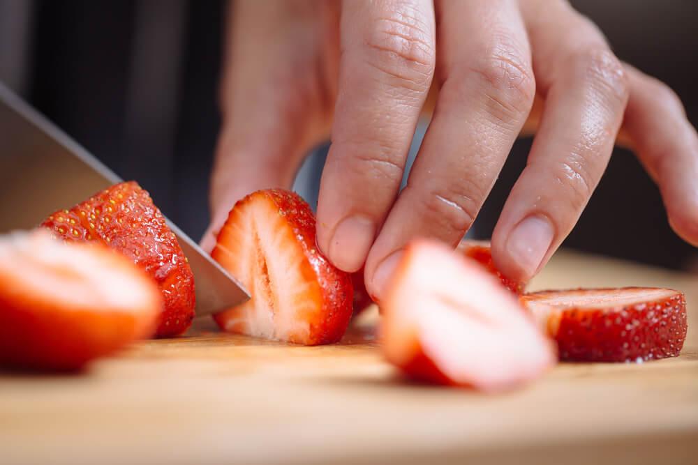 Hand cutting strawberries
