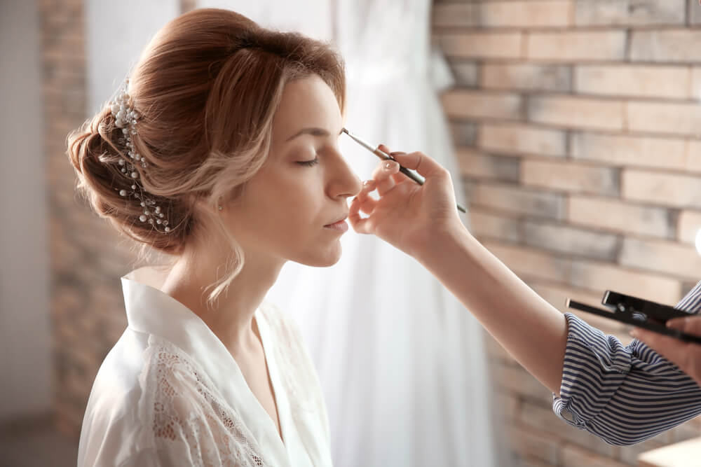 Makeup artist doing makeup on woman