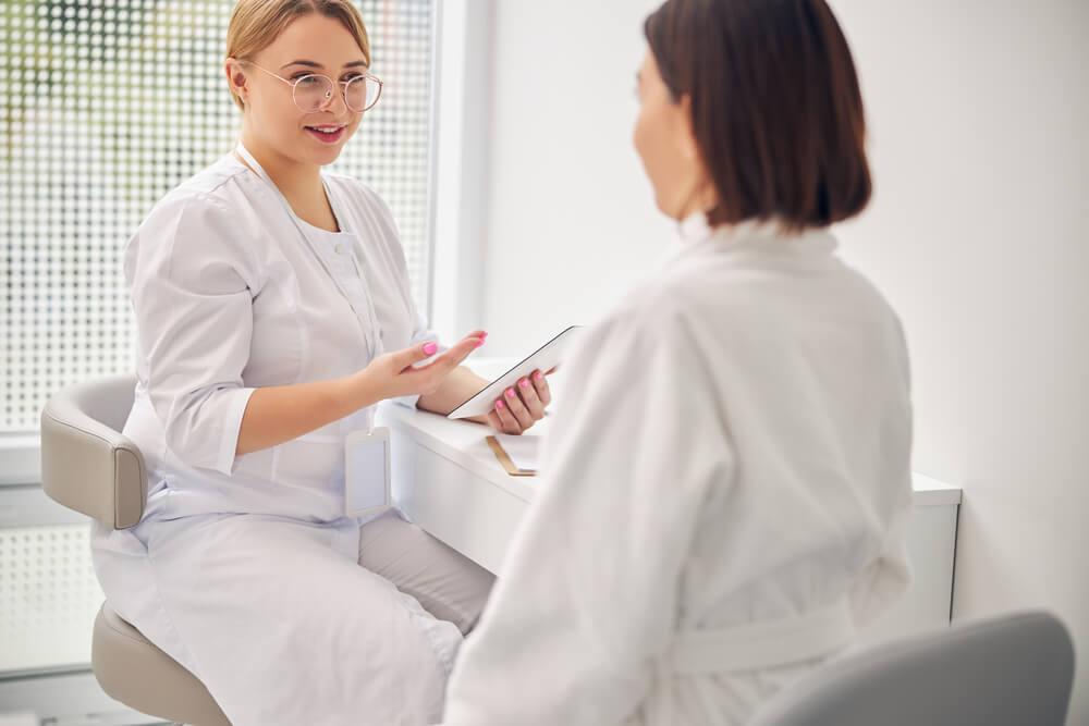 Dermatologist talking to woman