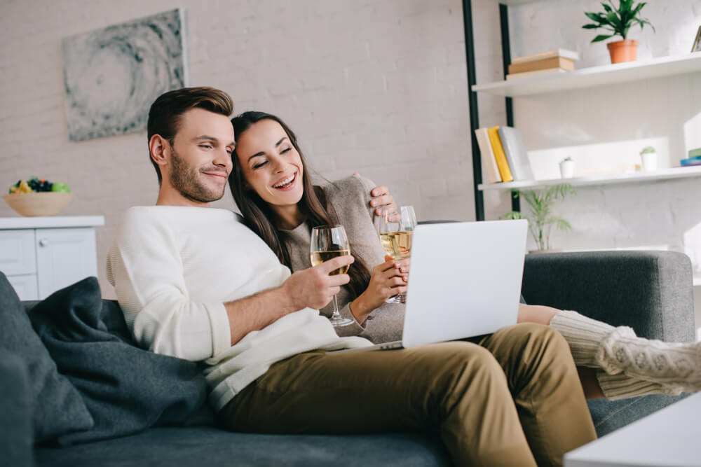 Couple with wine laughing at laptop