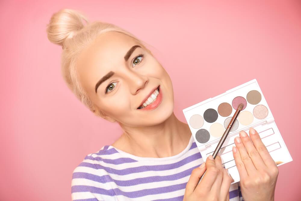 Woman pointing at pink eyeshadow